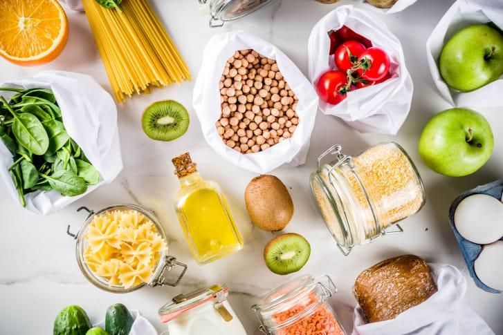 На белой поверхности лежат различные экологичные продукты: фрукты, овощи, крупы, макароны, хлеб.